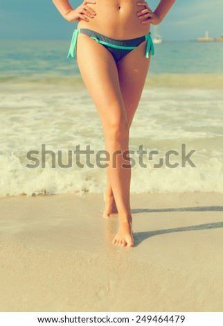 Close-up view of women's legs on the beach. - stock photo