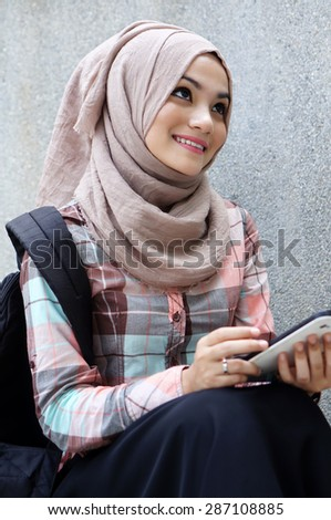 Close up view of young muslim girl student with her tablet - stock photo