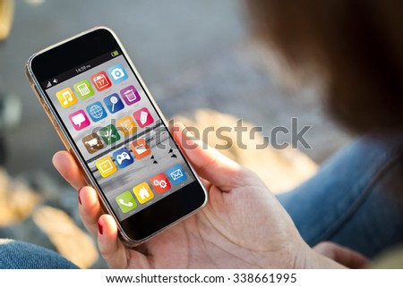 close-up view of young woman checking her mobile phone. All screen graphics are made up. - stock photo