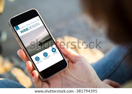 close-up view of young woman checking her mobile phone with web design site. All screen graphics are made up. - stock photo