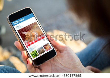 close-up view of young woman checking influencer profile on her mobile phone. All screen graphics are made up. - stock photo