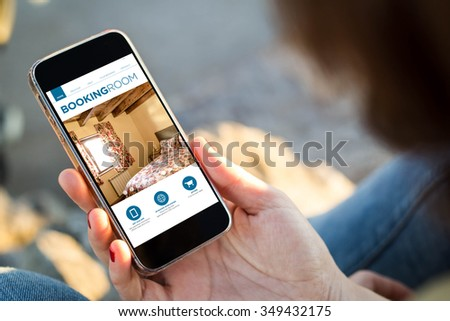 close-up view of young woman holding a smartphone with booking room app on screen. All screen graphics are made up. - stock photo