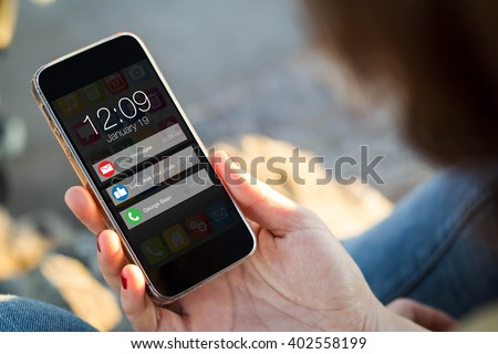 close-up view of young woman looking at notifications on her mobile phone. All screen graphics are made up. - stock photo