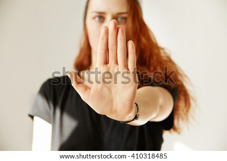 Close up view of young woman making stop gesture with her hand. Cropped isolated portrait of redhead female in cap and black T-shirt standing against white background. - stock photo