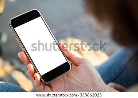 close-up view of young woman using her mobile phone with blank screen - stock photo