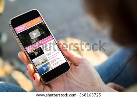 close-up view of young woman watching videos on her mobile phone. All screen graphics are made up.