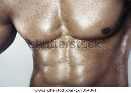 Close-up view on a muscular man's torso - stock photo