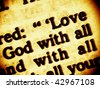 Close up view on a part biblical commandment of unconditional love to God and the neigbour. Focusing on the words: Love - God with all. Bible -Gospel of Luke ch. 10, v. 27. (Bible in Macro series) - stock photo