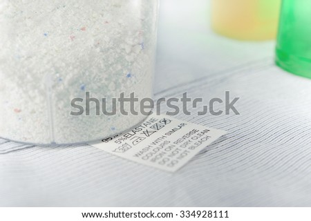 Close up view on an washing label tag and washing powder . - stock photo