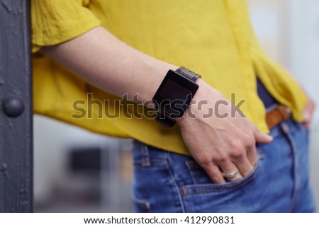 Close up view on blank screen smart watch on wrist of persons hand partially inserted into jeans pocket - stock photo