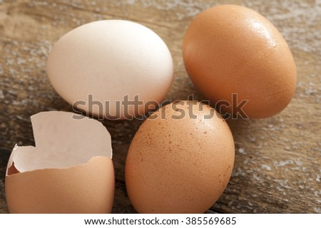 Close up view on brown, white and cracked open egg types on old wooden table - stock photo