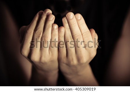 Close up view on pair of hands with palms up in prayer according to Islamic tradition - stock photo