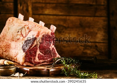 Close up view on raw cote de boeuf beef rib portion with rosemary over wooden plate and rustic background - stock photo