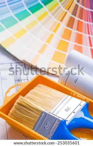 close up view on two paintbrushes in paint can and color palette with blueprints