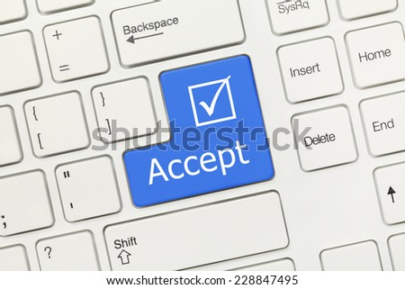 Close-up view on white conceptual keyboard - Accept (blue key)