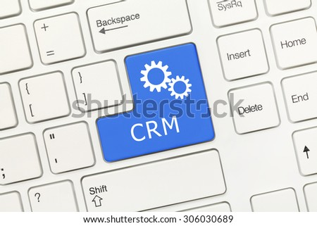 Close-up view on white conceptual keyboard - CRM (blue key with gear symbol) - stock photo
