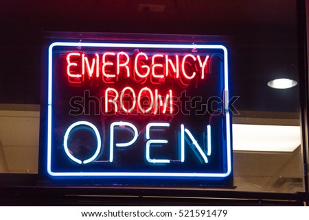 Close-up view Open neon or led sign of an emergency room illuminated at night in Houston, Texas, US. Red Emergency department entrance with neon shining signboard. Emergency healthcare service concept