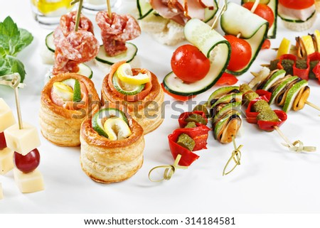 close-up view set of canapes with vegetables, salami, seafood, meat and decoration on whie plate studio isolated - stock photo