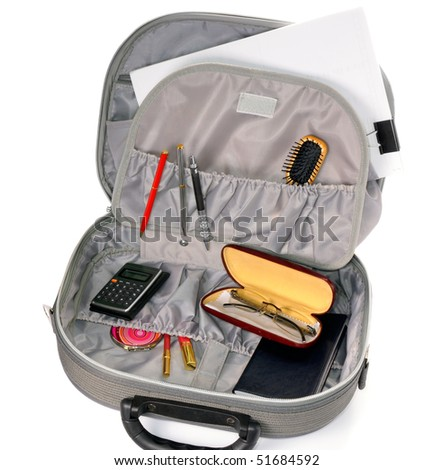 Close-up view to opened suitcase with accessories on white background. Studio shot, not isolated.