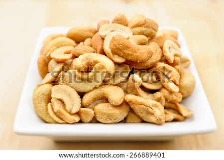 Close-up view to salted cashew nuts on a white plate on wooden background. - stock photo