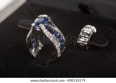 Close-up view to silver diamond ring with blue gem - stock photo