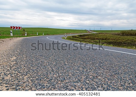 Close-up view to the curvy road among green meadows - stock photo