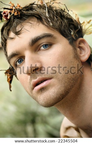 Close-up warm portrait of beautiful young man in nature with leaves and branches in his hair - stock photo