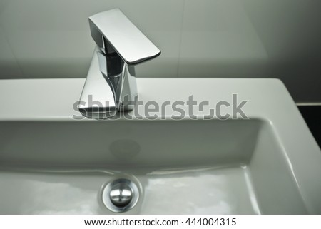 Close up Water tap and square basin.