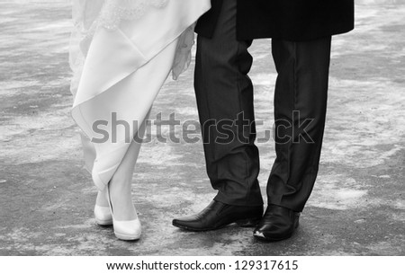 Close-up wedding shoes of bride and groom in outdoor. Black and white. - stock photo
