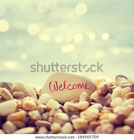 """Close Up """"Welcome"""" Text Written on the Stone at the Beach. Sea Pebble with Shallow Depth of Field and Beautiful Bokeh. Toned Photo. - stock photo"""