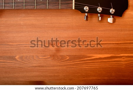 Close-up western guitar neck on wooden background - stock photo
