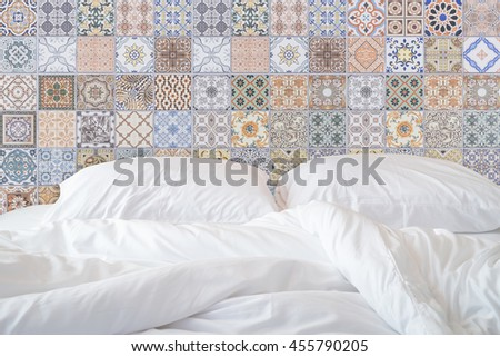 Close up white bedding sheets and pillow on natural stone wall room background, Messy bed concept - stock photo
