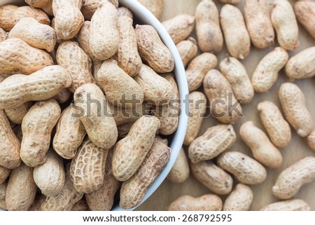 close up white bowl full of peanuts - stock photo