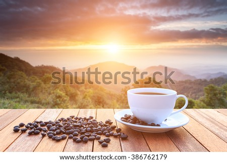 Close up white coffee cup and coffee beans on wood table and view of sunset or sunrise background