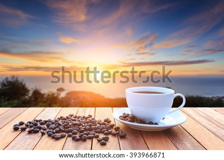 Close up white coffee cup and coffee beans on wood table and view of sunset or sunrise background - stock photo