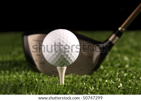 Close up white golf ball on white tee secured in green grass(artificial turf) with 1 wood driver (golf club) behind the ball ready to be hit, black background, space for copy to be added.
