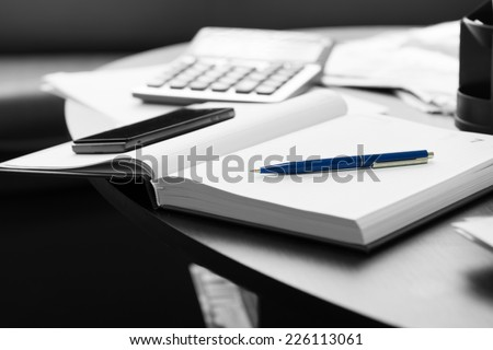 Close up White Memo Notebook with Blue Pen and Mobile Phone on Black Round Table. - stock photo
