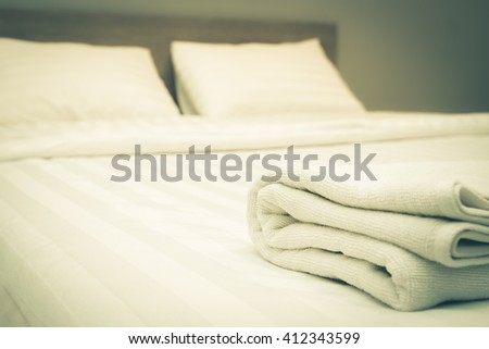 Close up white towels lying on the bed , vintage tone