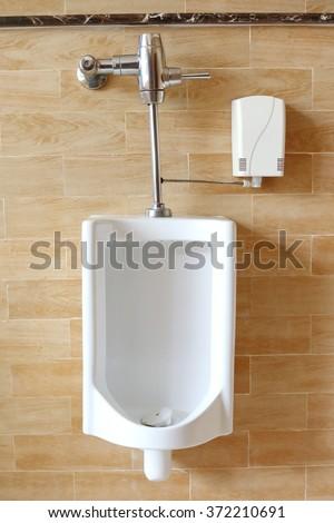 Close-up white urinals in men's public restroom. - stock photo