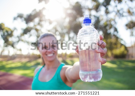 Close up wide angle view of a female fitness athlete holding up a bottle of water with a smile on her face. Back light natural light. - stock photo