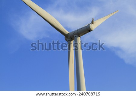 close up wind turbine against partly cloudy blue sky - stock photo