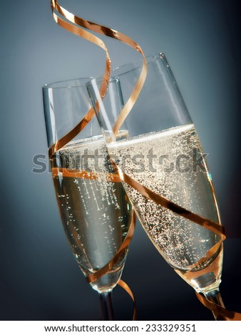 Close up Wines on Elegant Flute Glasses with Gold Laces Design on Gradient Blue Gray Background. A New Years Day Concept Design. - stock photo