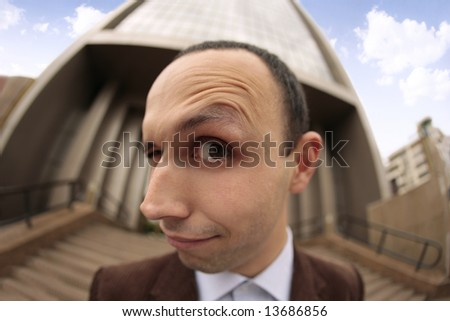 close up with a fish eye of a business man's eye and face with the eyebrow raised and smiling outside of an office building in Cluj-Napoca