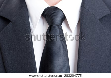 Close up with black suit and tie and white shirt