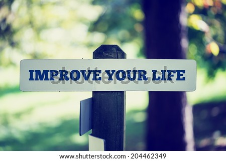 Close-up with selective focus on a sign pole with the inspirational advice to improve your life, outdoors, in a green area. - stock photo