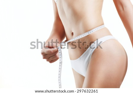 Close up woman body in white underwear with measurement line in hand against white background - stock photo