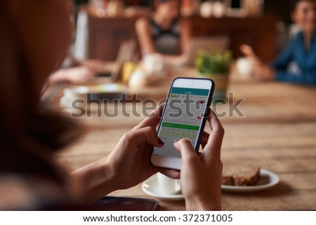 Close Up Woman Checking Activity App On Smart Phone In cafe - stock photo