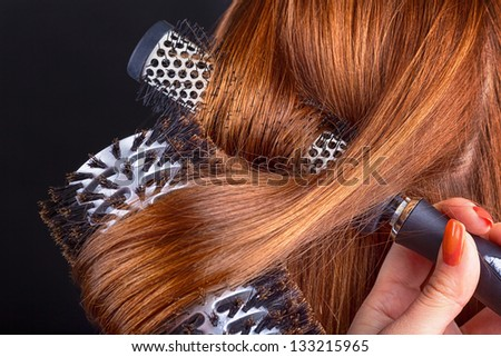 Close up woman combing hair on a dark background - stock photo