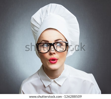 Close-up woman cook look round or hear something, over gray wall - stock photo