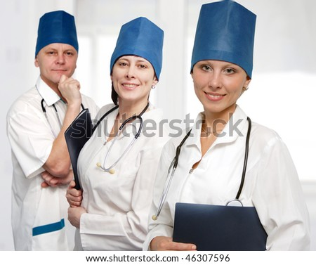 Close up woman doctor smiles and two doctors behind. - stock photo